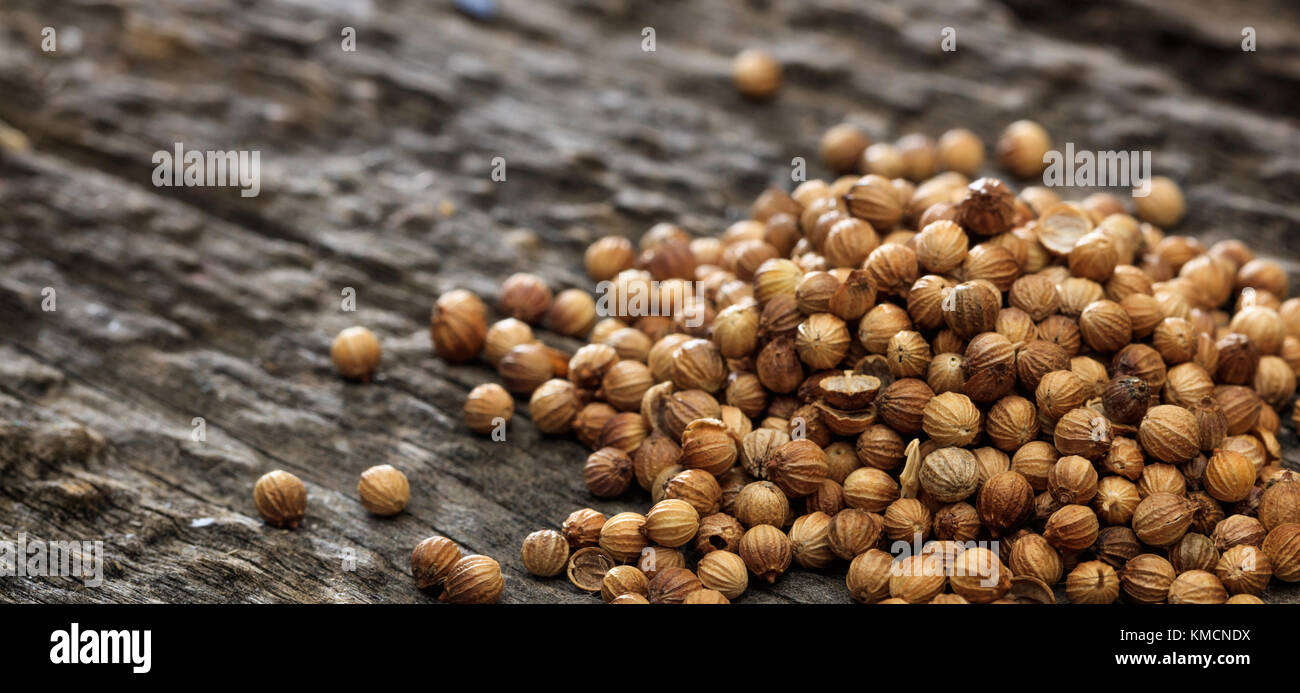 Dried coriander seeds in a pile set on old wooden surface. Closeup view and copyspace for text. - Stock Image
