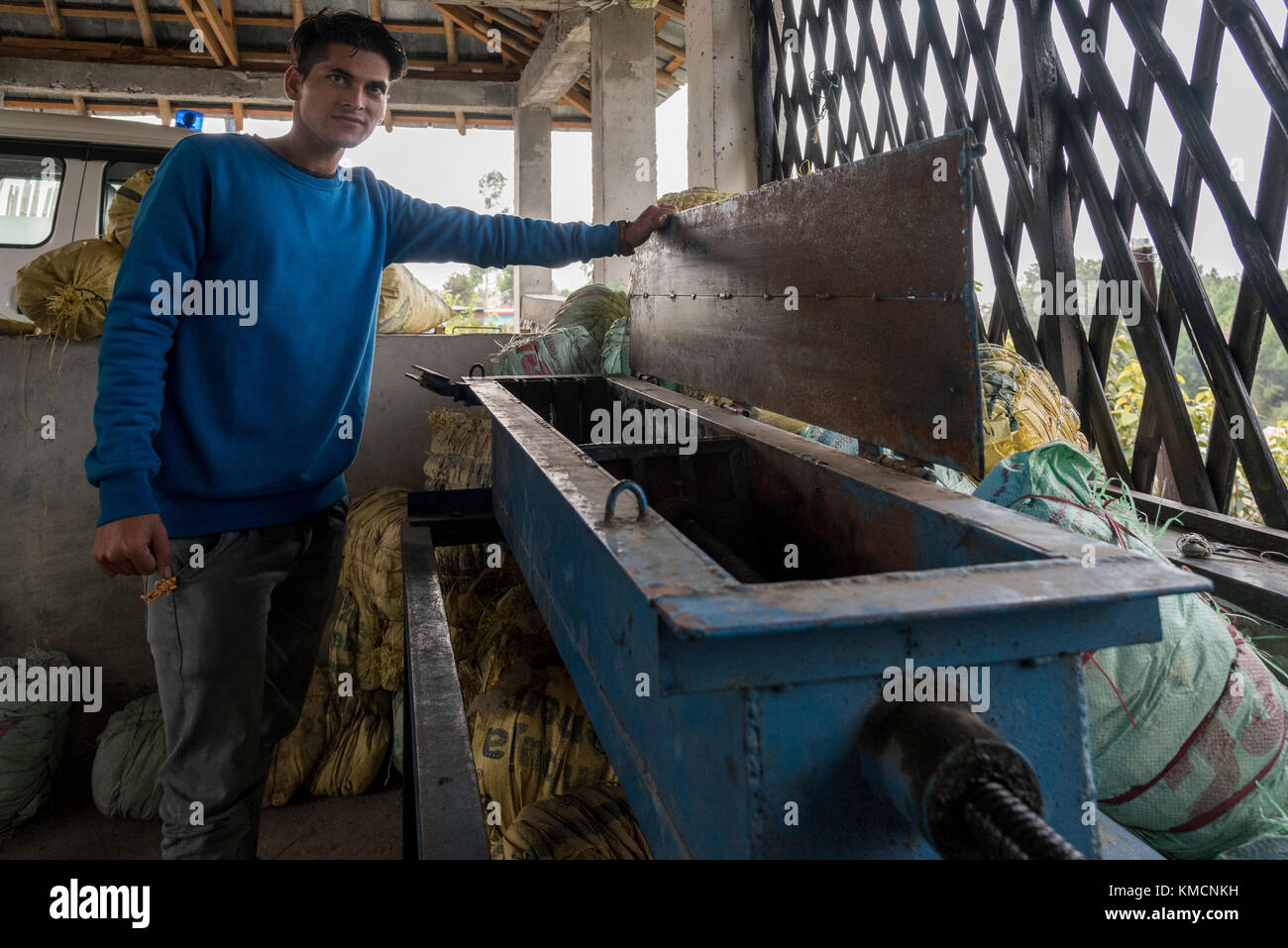 A young Indian boy demonstrates the use of waste plastic management machine in a village. - Stock Image