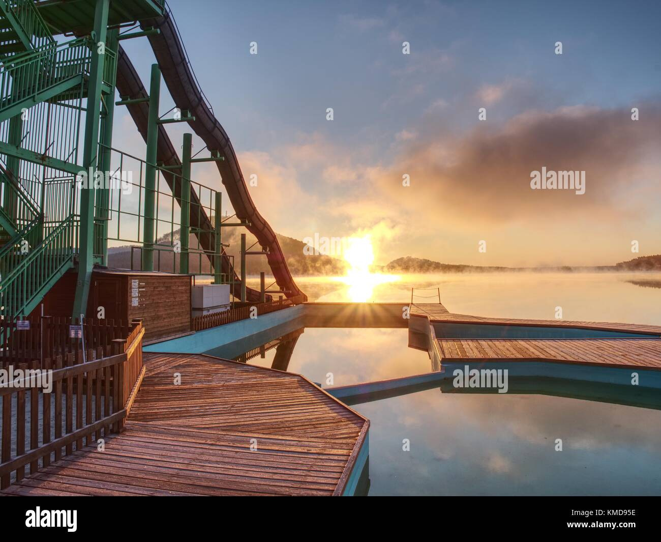 Sunset shore and toboggan slides at lake,. High ladder tower with  sliding track. Cold autumn morning with vapory Stock Photo
