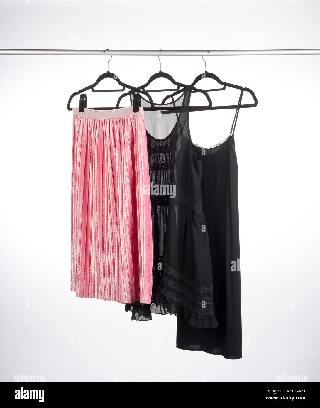 clothes on hangers, hanging on a clothes rail. - Stock Image