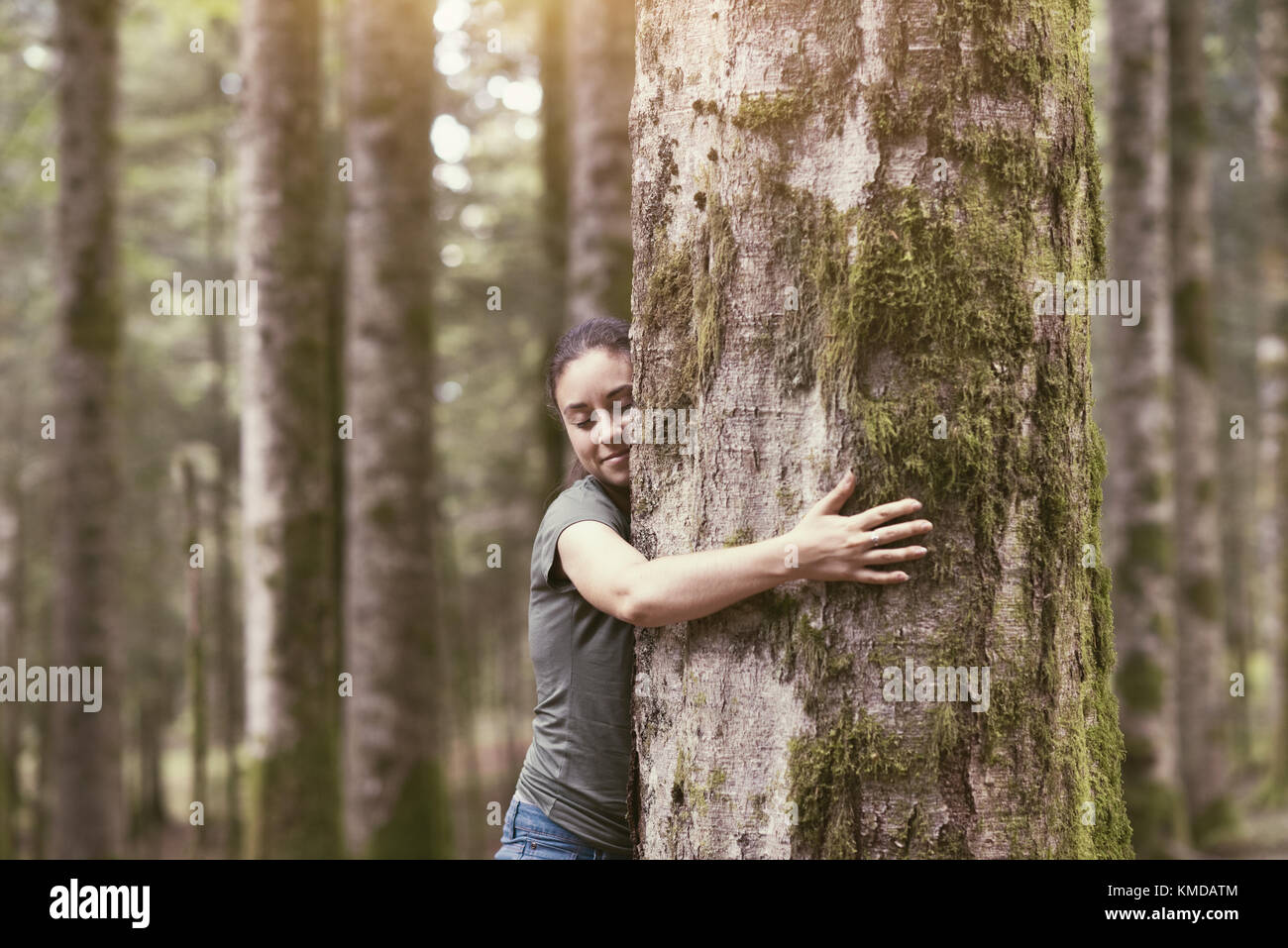 Smiling woman hugging a tree in a lush forest, environmental care and sustainability concept - Stock Image