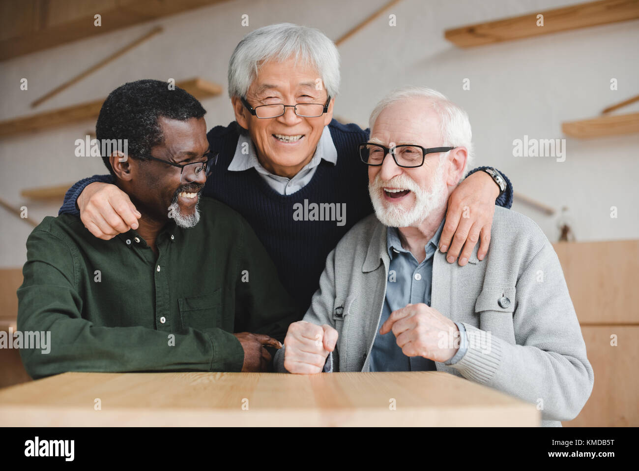 senior friends embracing in bar - Stock Image