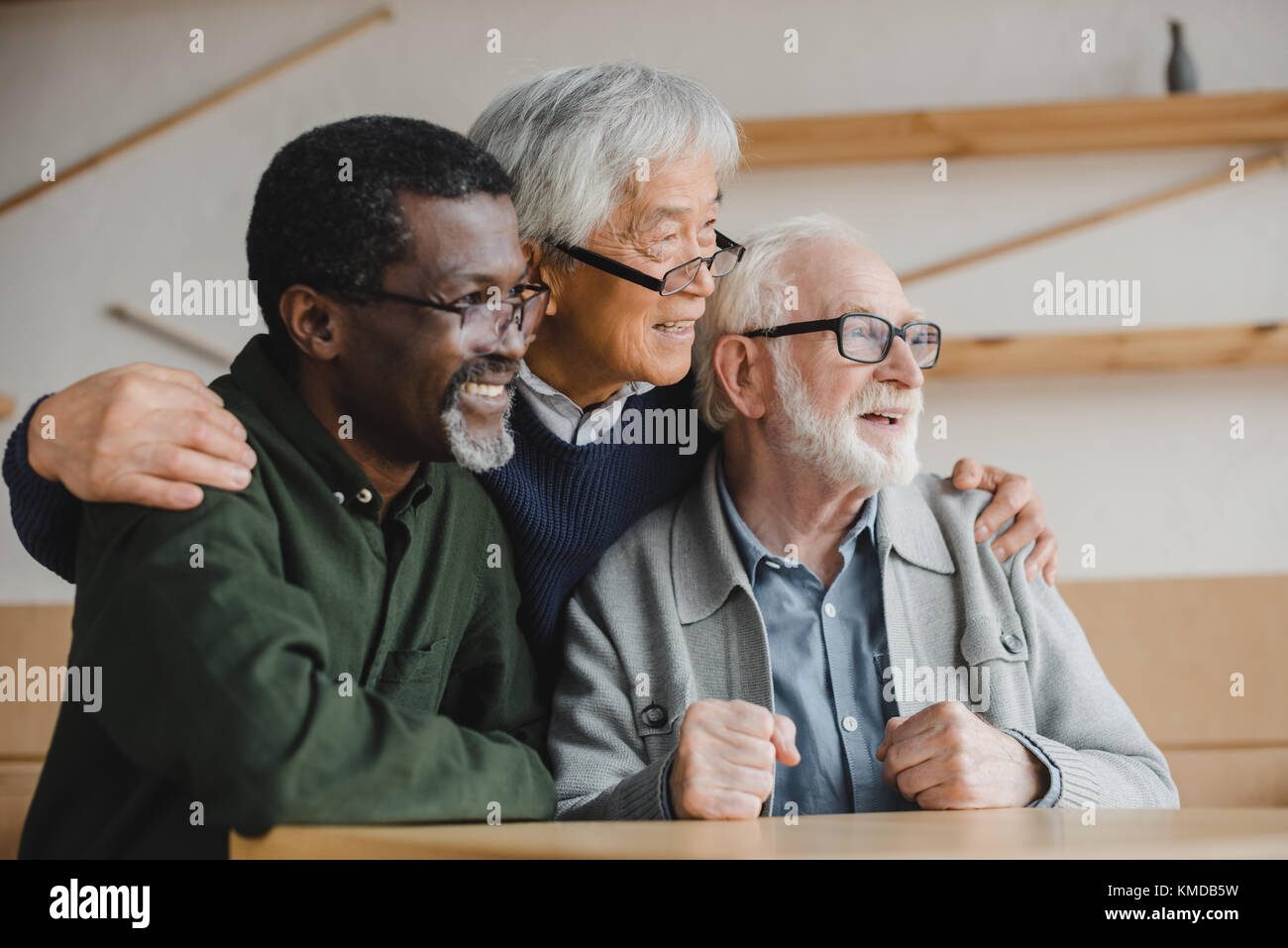 senior friends embracing and looking away - Stock Image