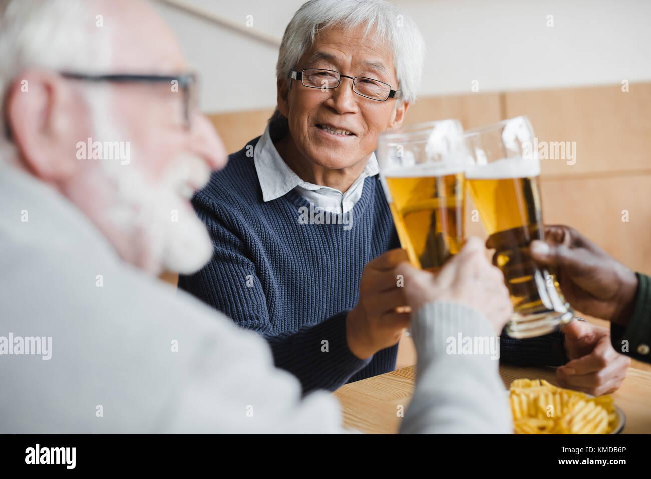 senior friends clinking glasses of beer - Stock Image