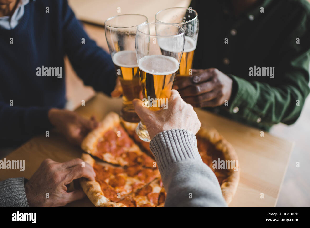 friends clinking glasses of beer - Stock Image
