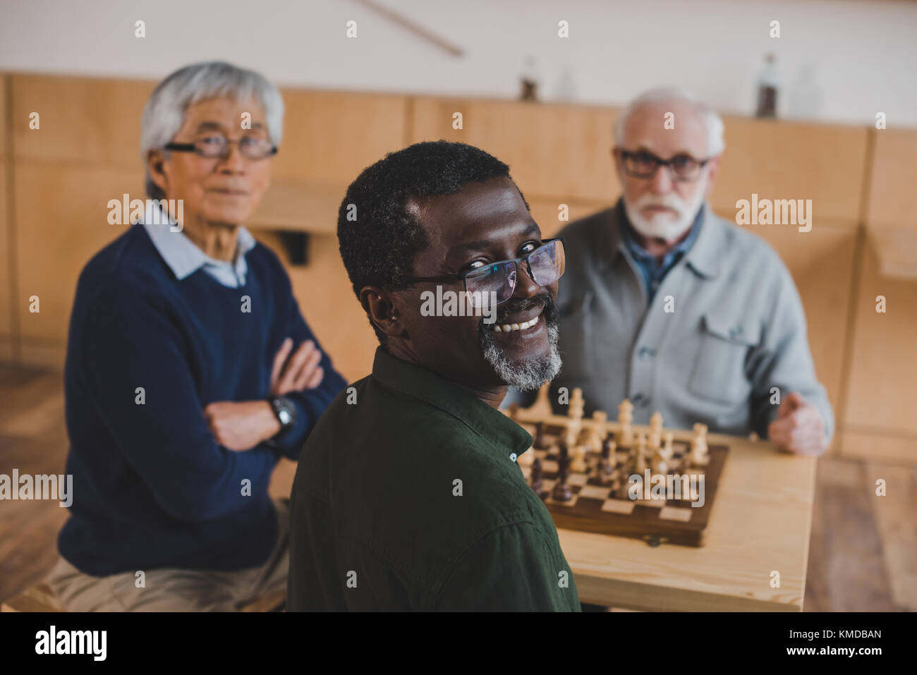 senior friends playing chess - Stock Image
