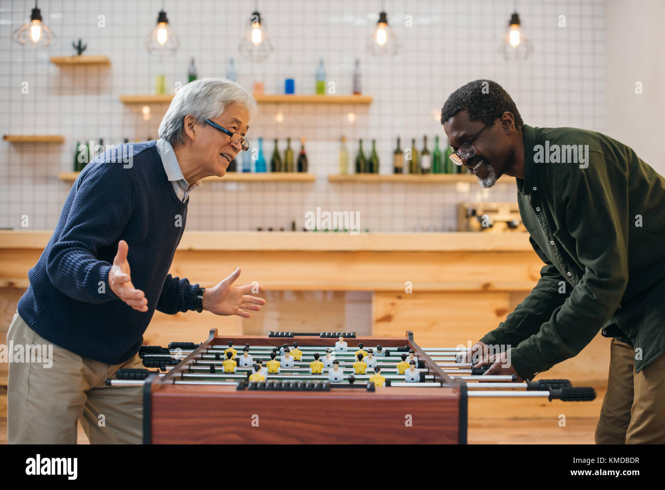 senior friends playing table football Stock Photo