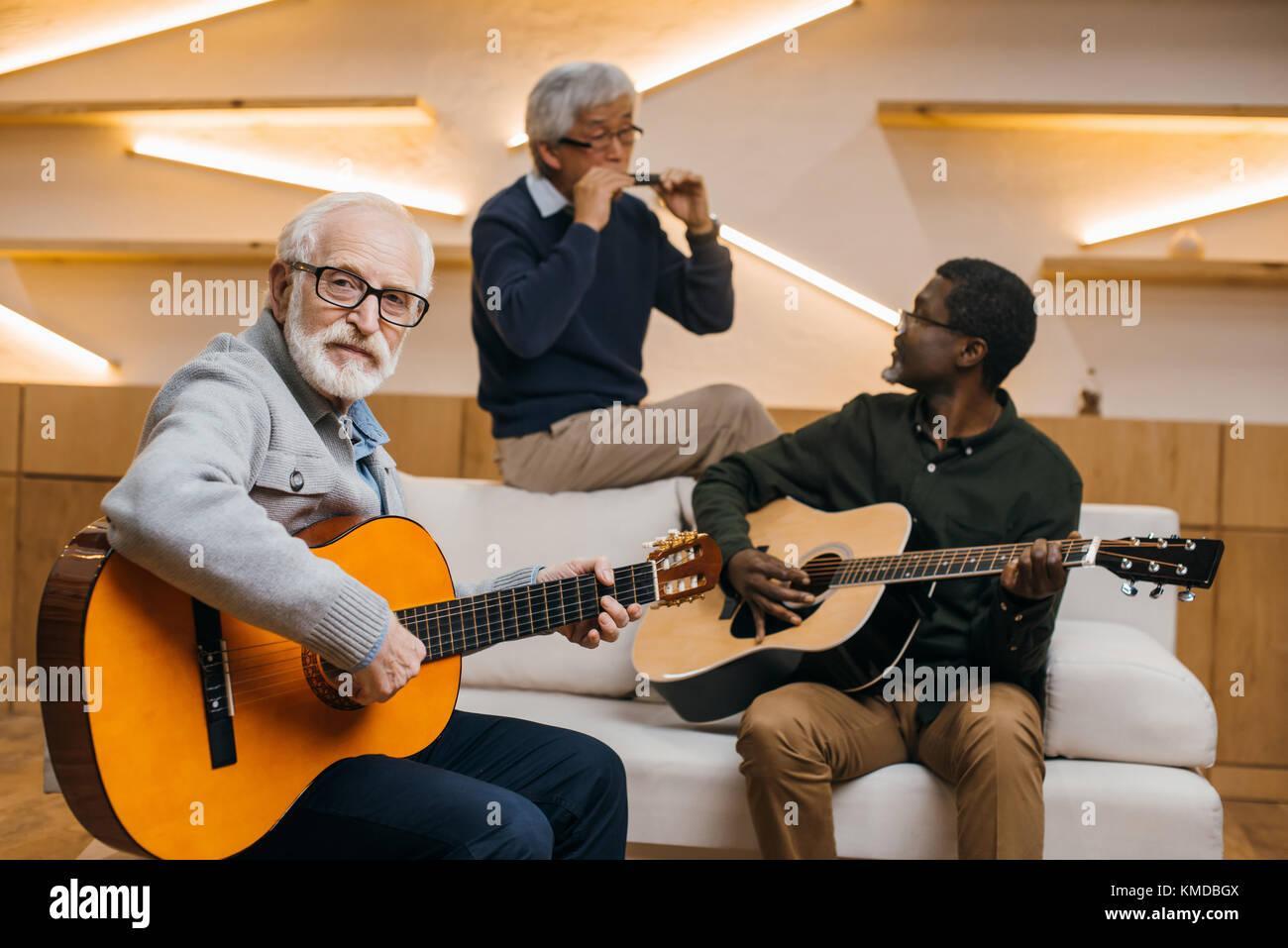 senior friends playing music - Stock Image
