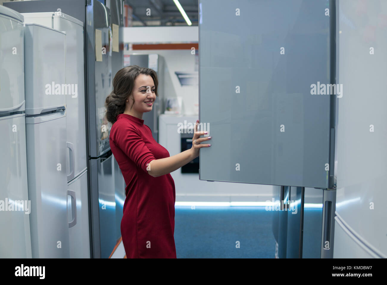 housewife choosing large fridges in domestic appliances section - Stock Image