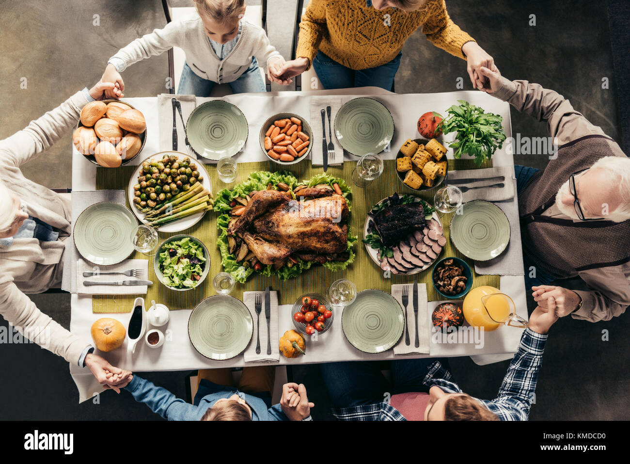 family praying before holiday dinner - Stock Image