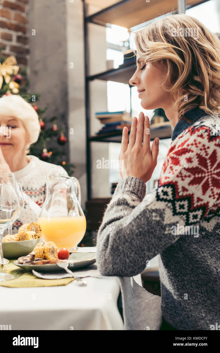 senior mother and daughter praying on christmas - Stock Image