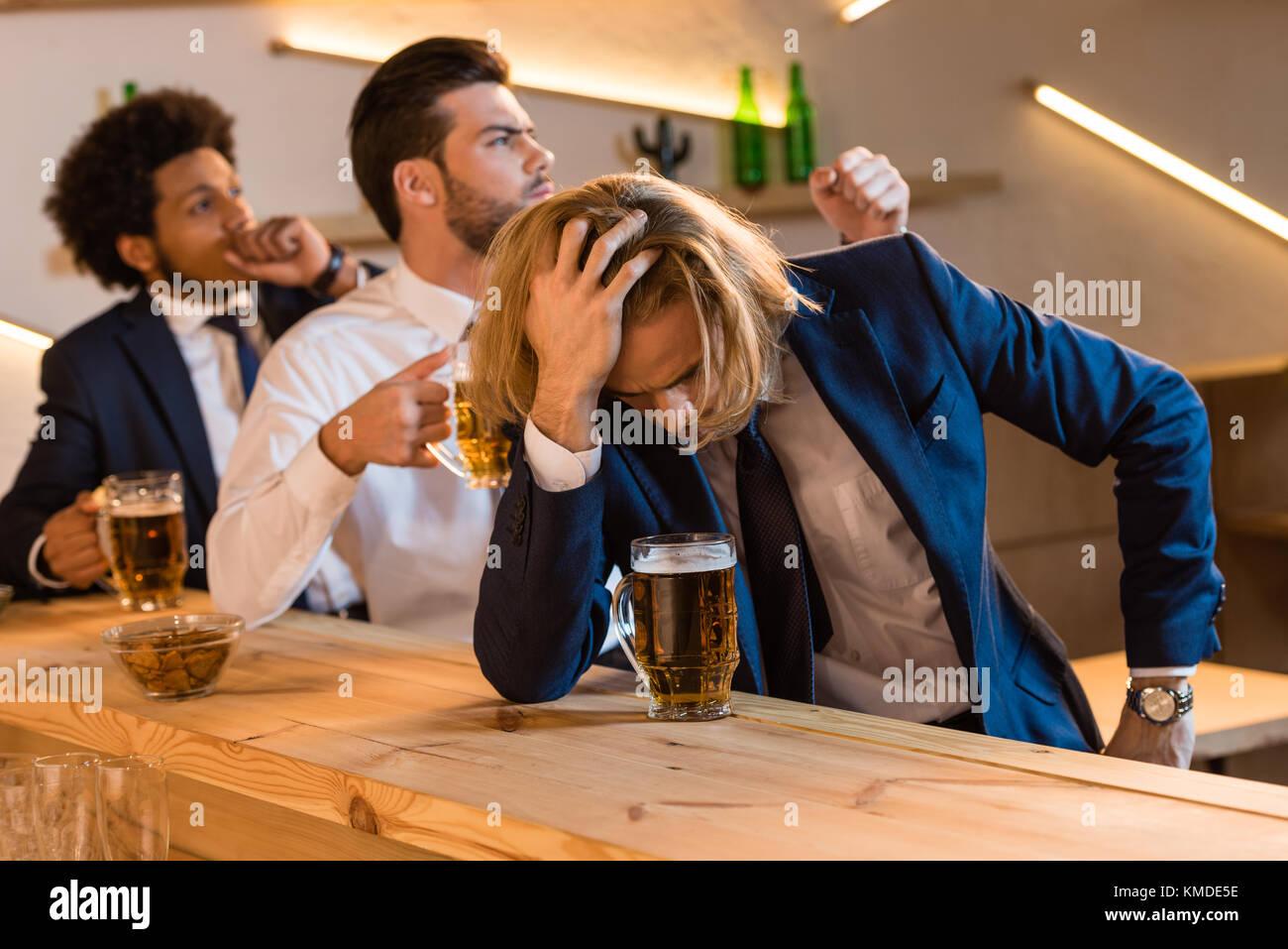 businessmen drinking beer in bar - Stock Image