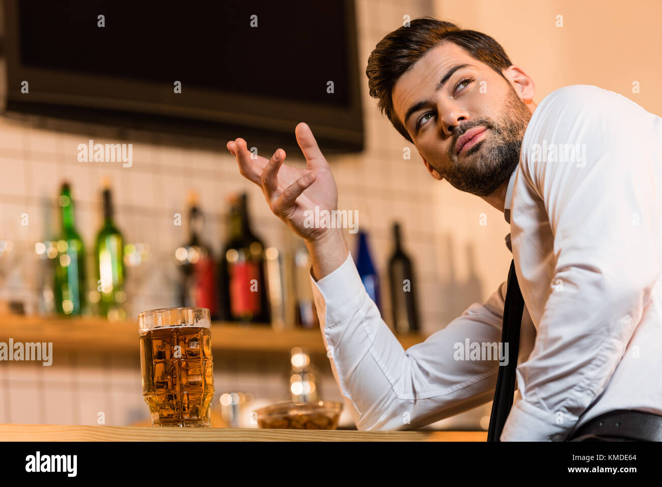 businessman with beer in bar - Stock Image