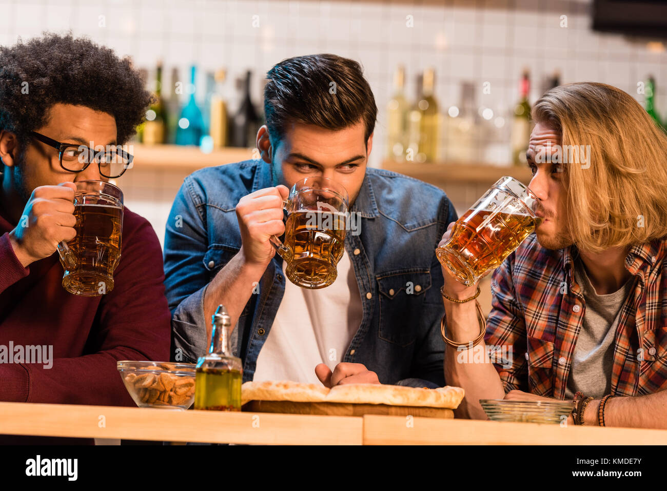 friends with pizza and beer in bar - Stock Image
