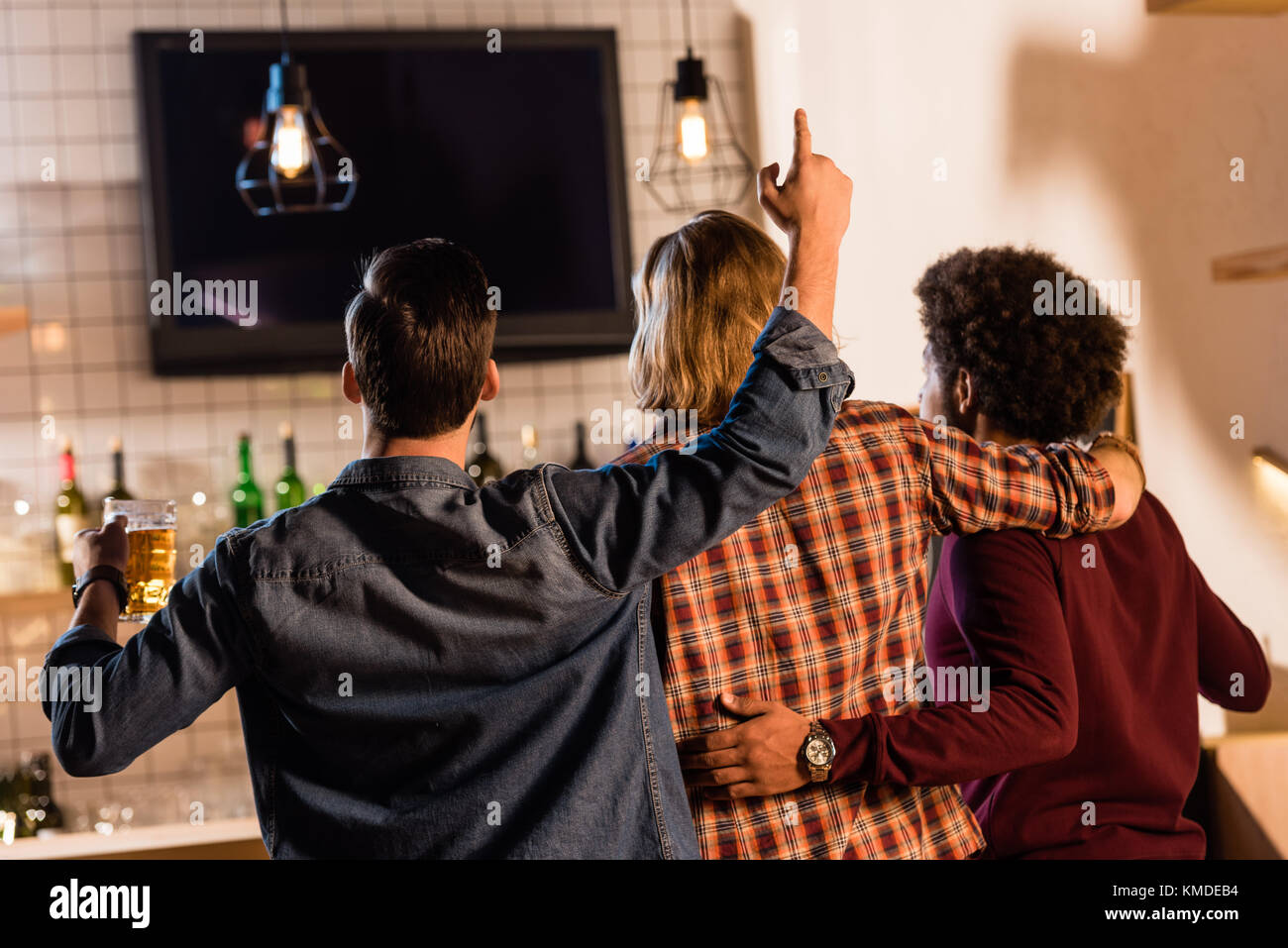 friends watching tv in bar - Stock Image