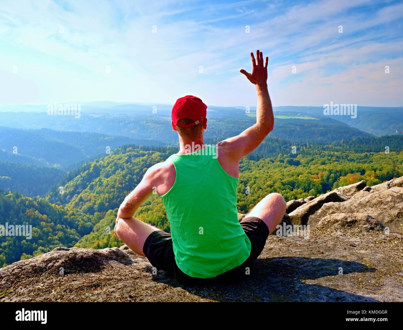 Slim body hiker in green singlet and black shorts sit on a rock, enjoy natural scenery. View into forest valley - Stock Image