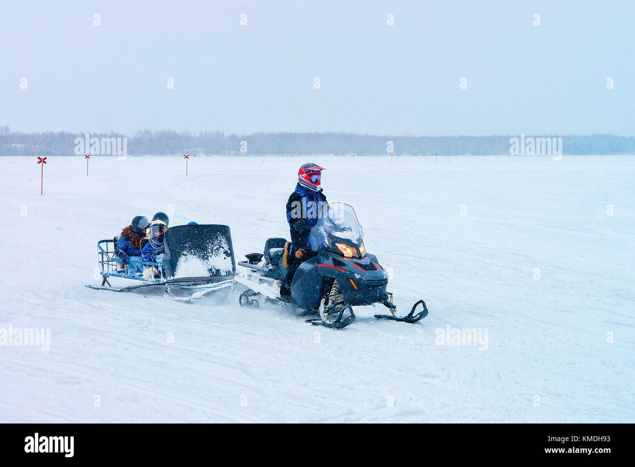 Man riding a snowmobile with kids in the frozen lake in