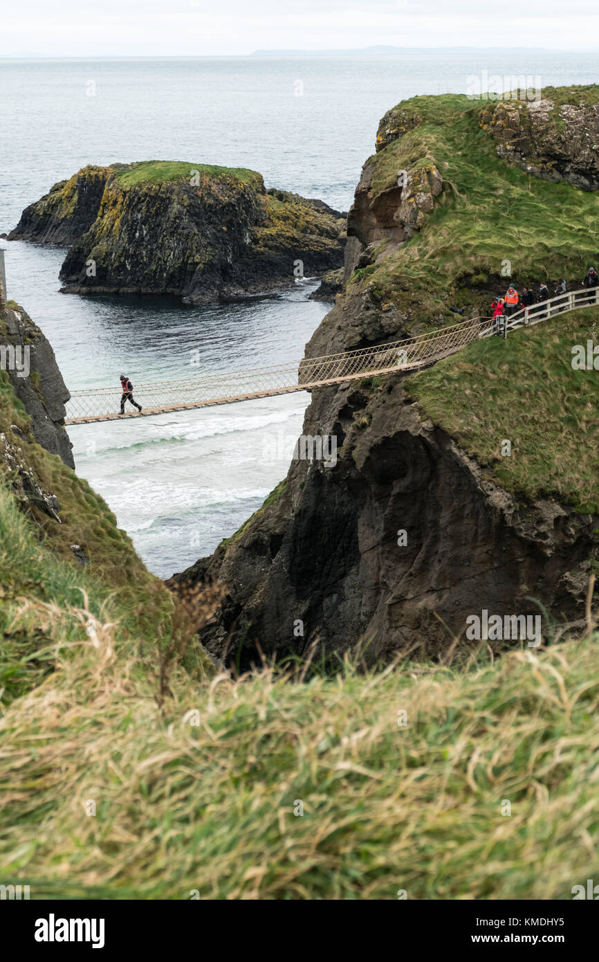 Visitors crossing the famous 'Carrick-a-Rede' bridge on the Causeway coast, Northern Island - Stock Image