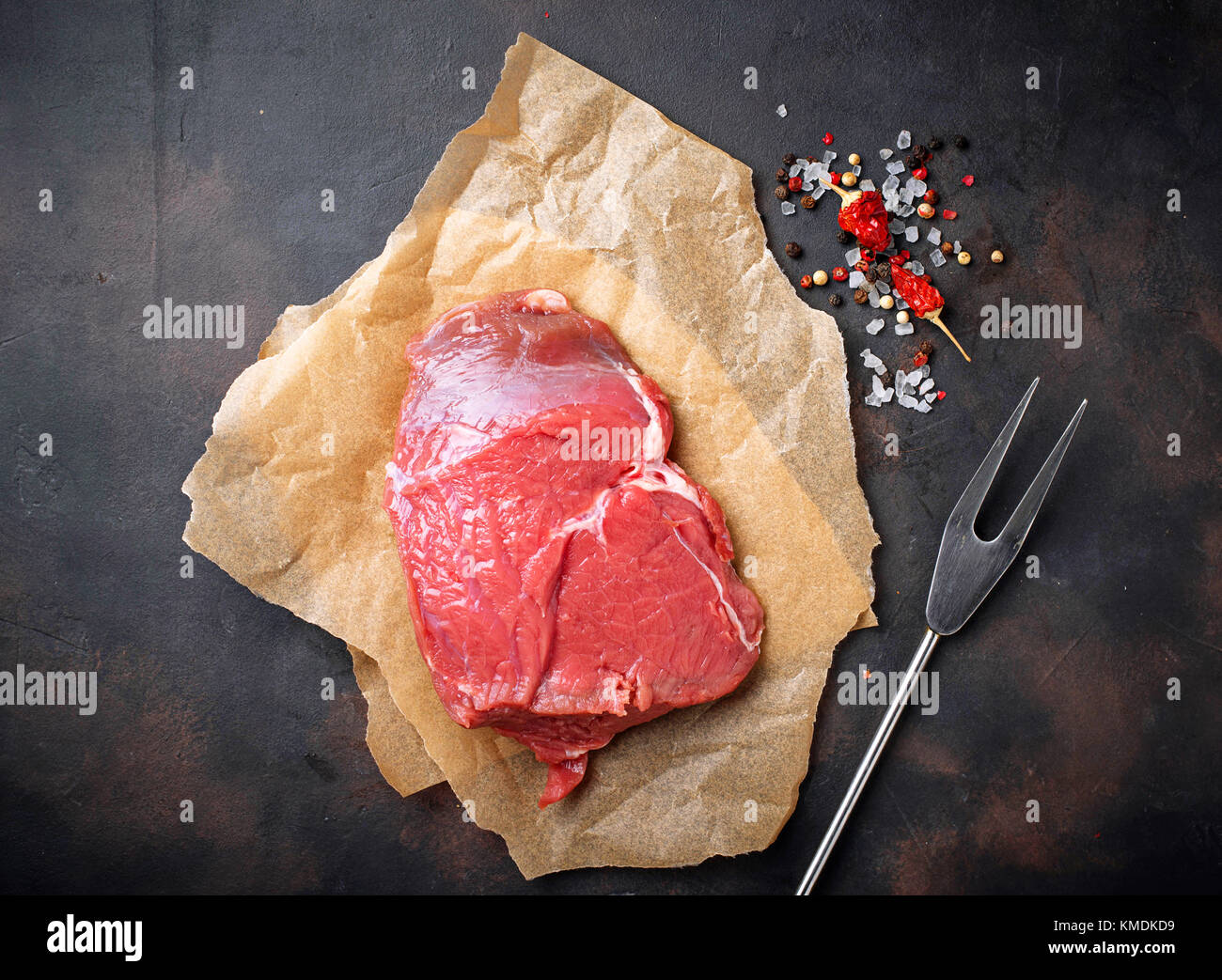 Raw meat steak with spices on rusty background - Stock Image