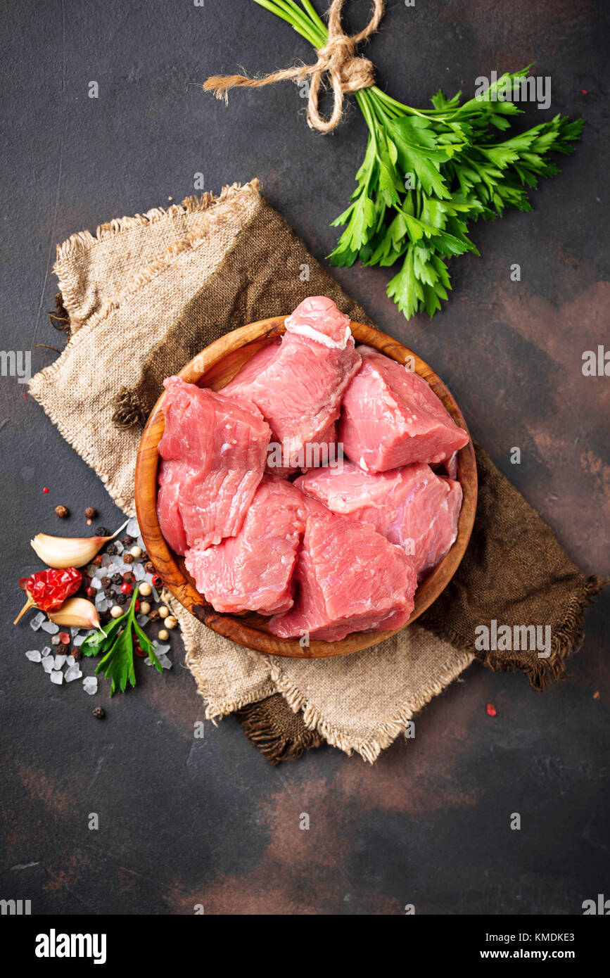 Raw chopped meat with spices on rusty background - Stock Image