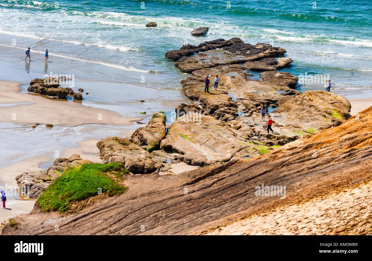 People explore the tidepools at Cape Kiwanda in Pacific City, Oregon. - Stock Image