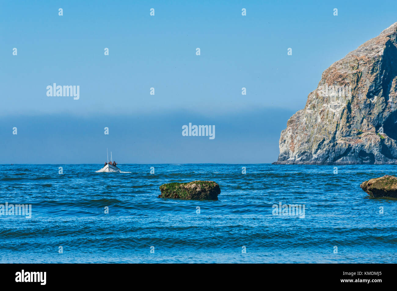 Pacific City, Oregon, USA - July 2, 2015: A dory boat passes by Haystack Rock as he makes his approach to land on - Stock Image