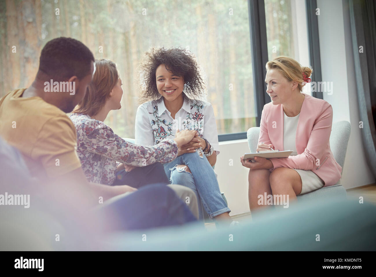 Smiling woman comforting woman in group therapy session - Stock Image