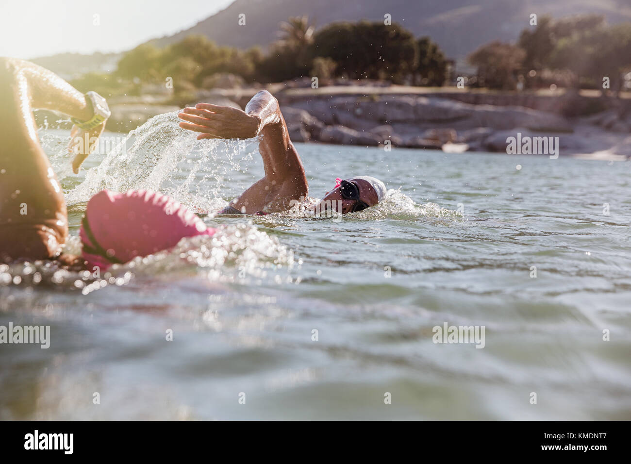 Female open water swimmers swimming in sunny ocean - Stock Image