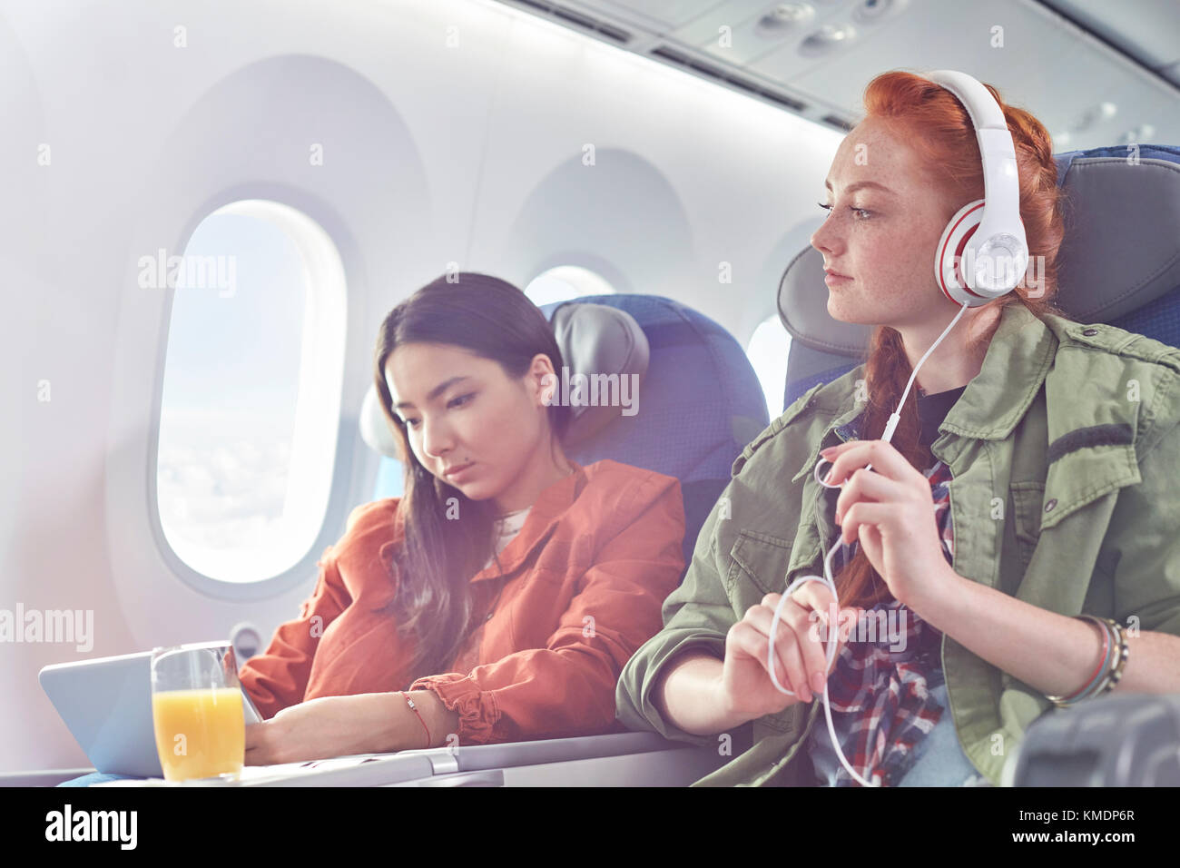 Young women friends with headphones and digital tablet on airplane - Stock Image