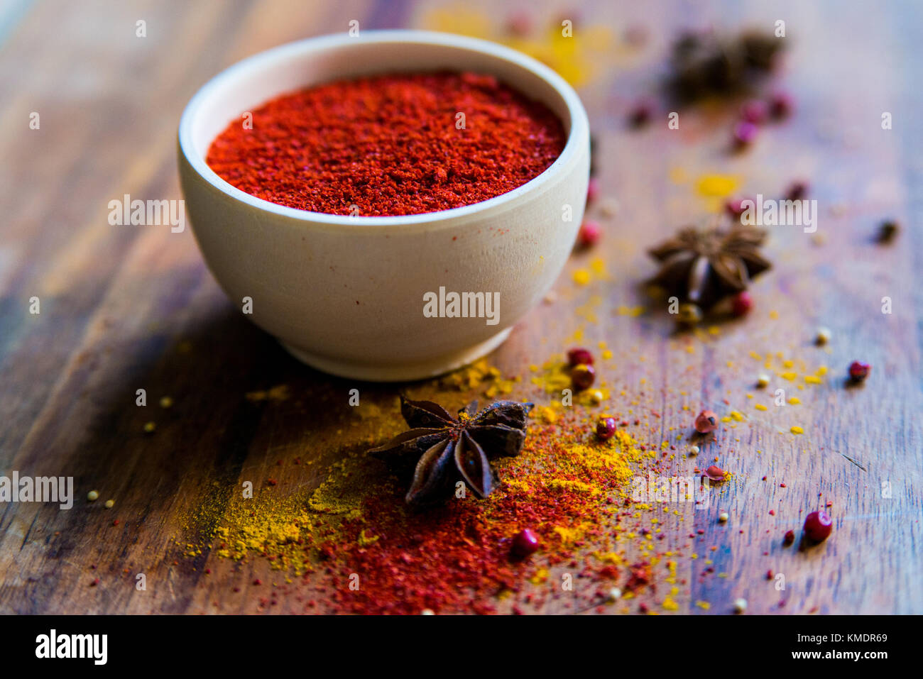 Paprika powder in wooden bowl with anise - Stock Image