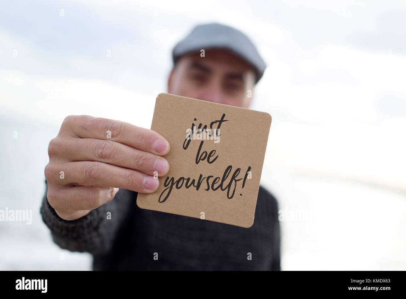 closeup of a young caucasian man wearing a flat cap outdoors shows a signboard with the text just be yourself written - Stock Image