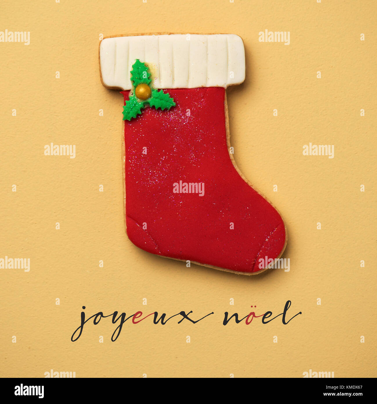 a coloroful cookie in the shape of a christmas stocking and the text joyeux noel, merry christmas in french, on - Stock Image