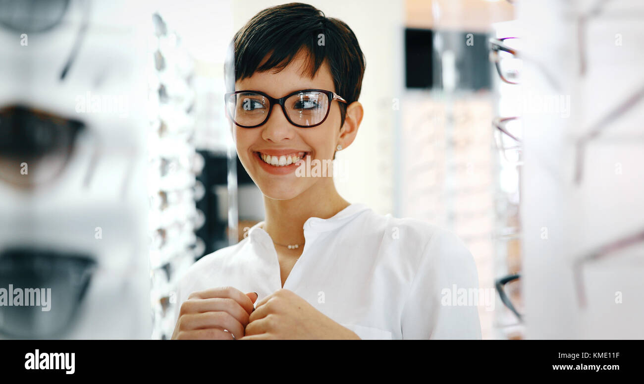 Beautiful woman with optician trying eyeglasses - Stock Image