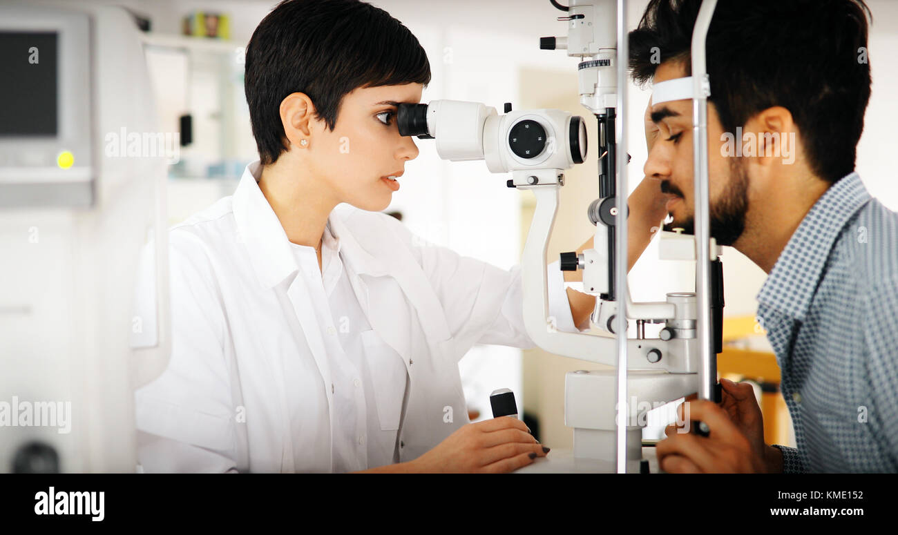 Woman doing eye test with optometrist in eye sight clinic - Stock Image