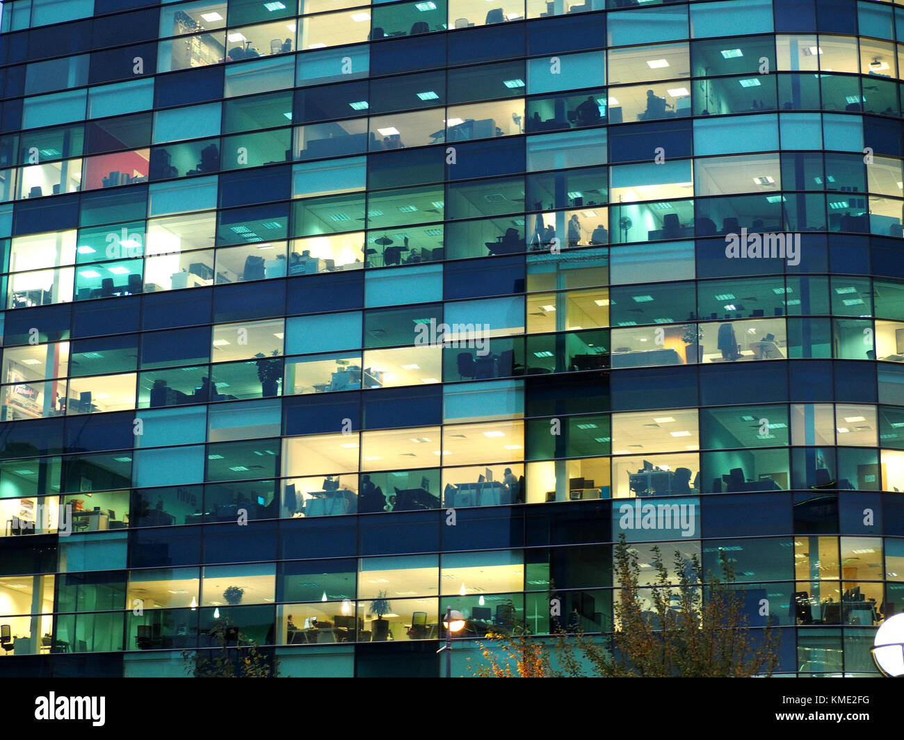 Last Few Office Workers At Dusk In Illuminated Offices In