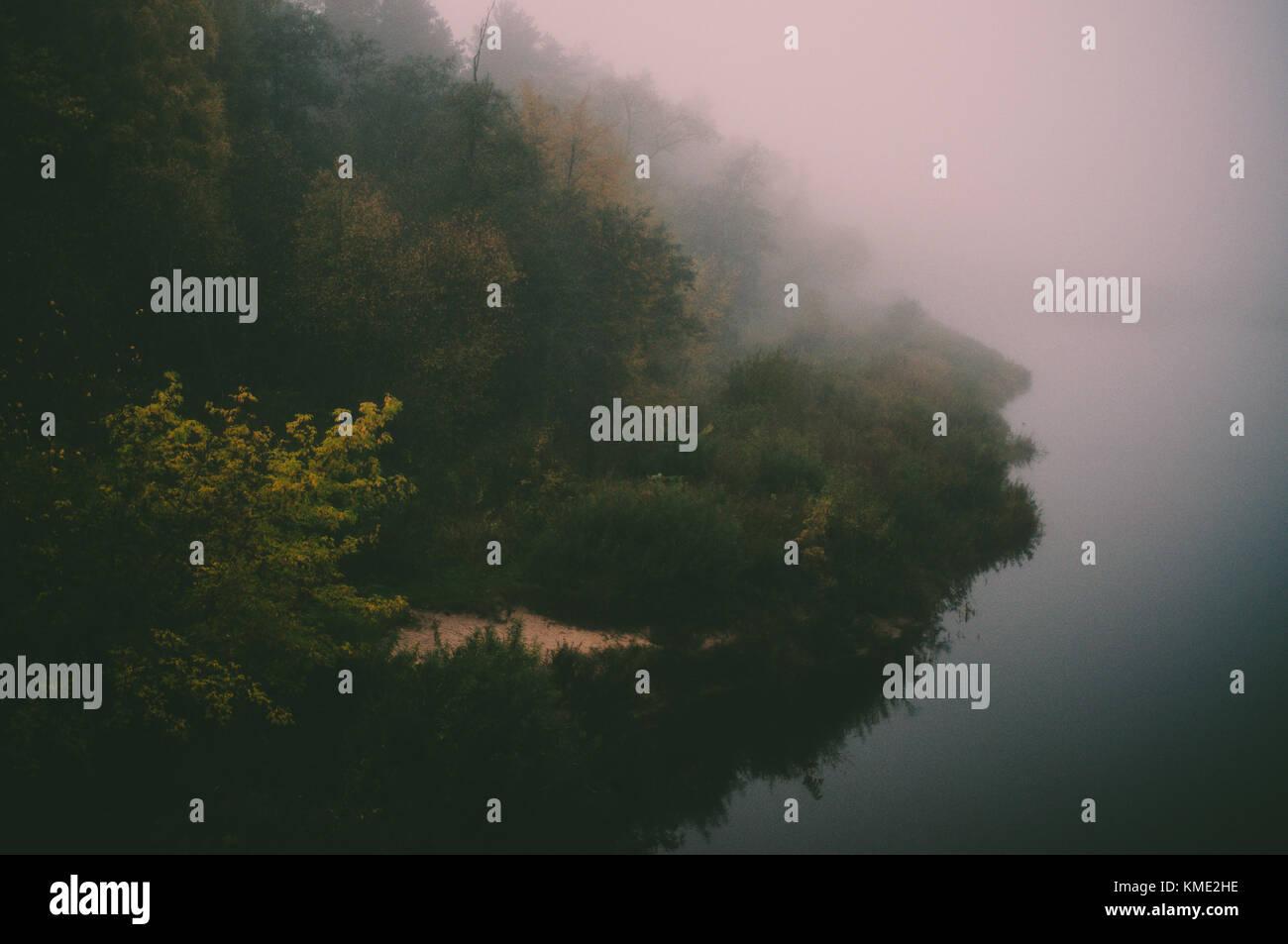 Misty morning on green island. Smoky mysterious landscape. - Stock Image