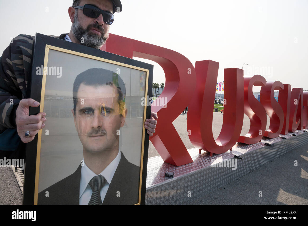 The man holds a portrait of President Bashar Assad near the inscription 'Russia 2018' in the Olympic Park - Stock Image