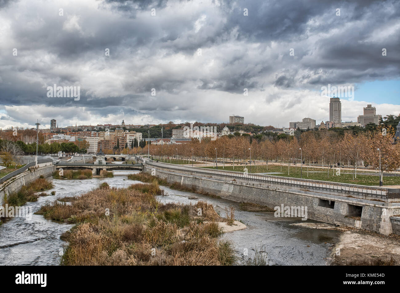 Skyline of Madrid (Spain) viewed from Segovia Bridge, including Manzanares river and Madrid Rio park. Stock Photo