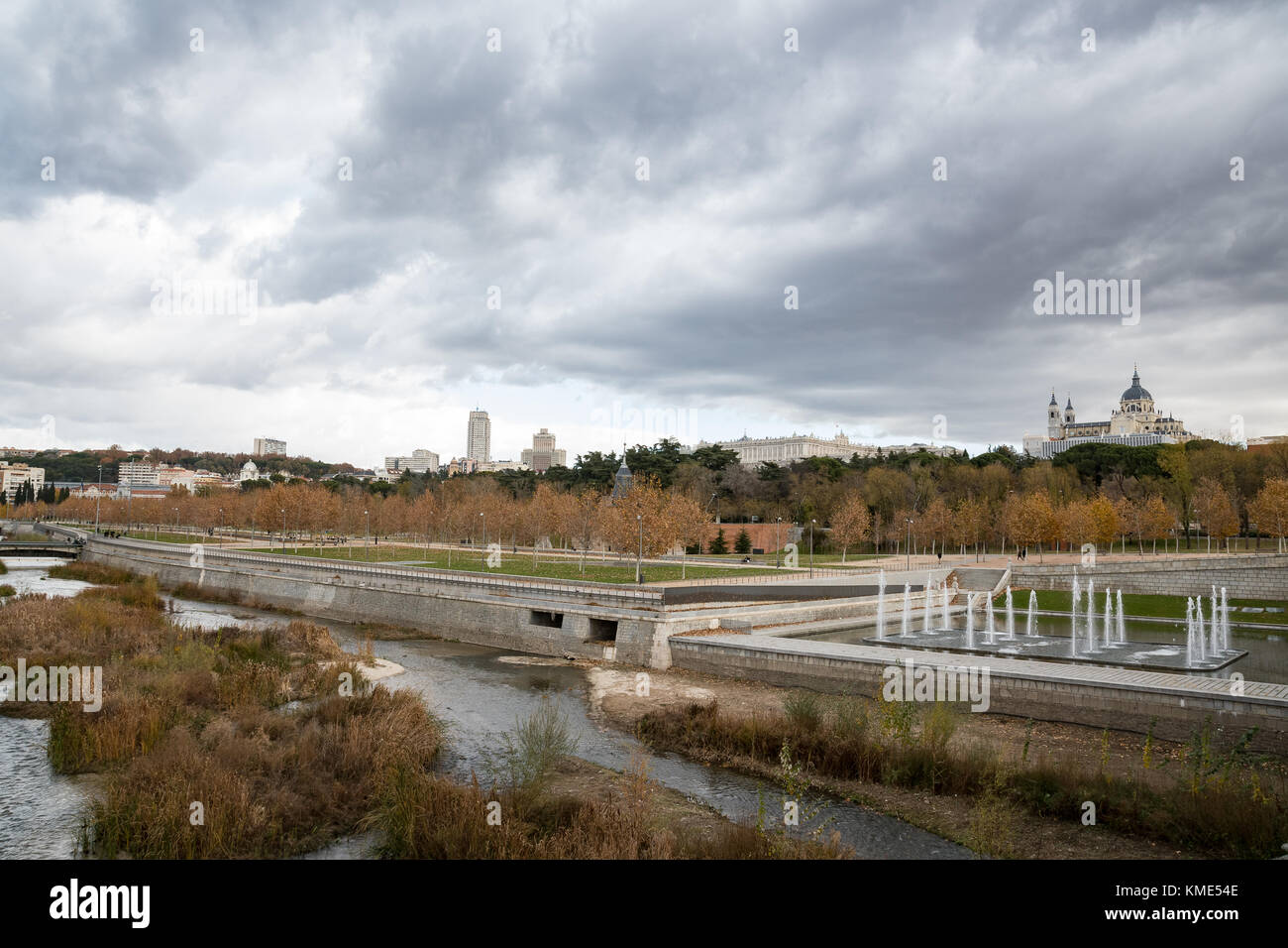 Skyline of Madrid (Spain) viewed from Segovia Bridge, including Manzanares river and Madrid Rio park. Stock Photo