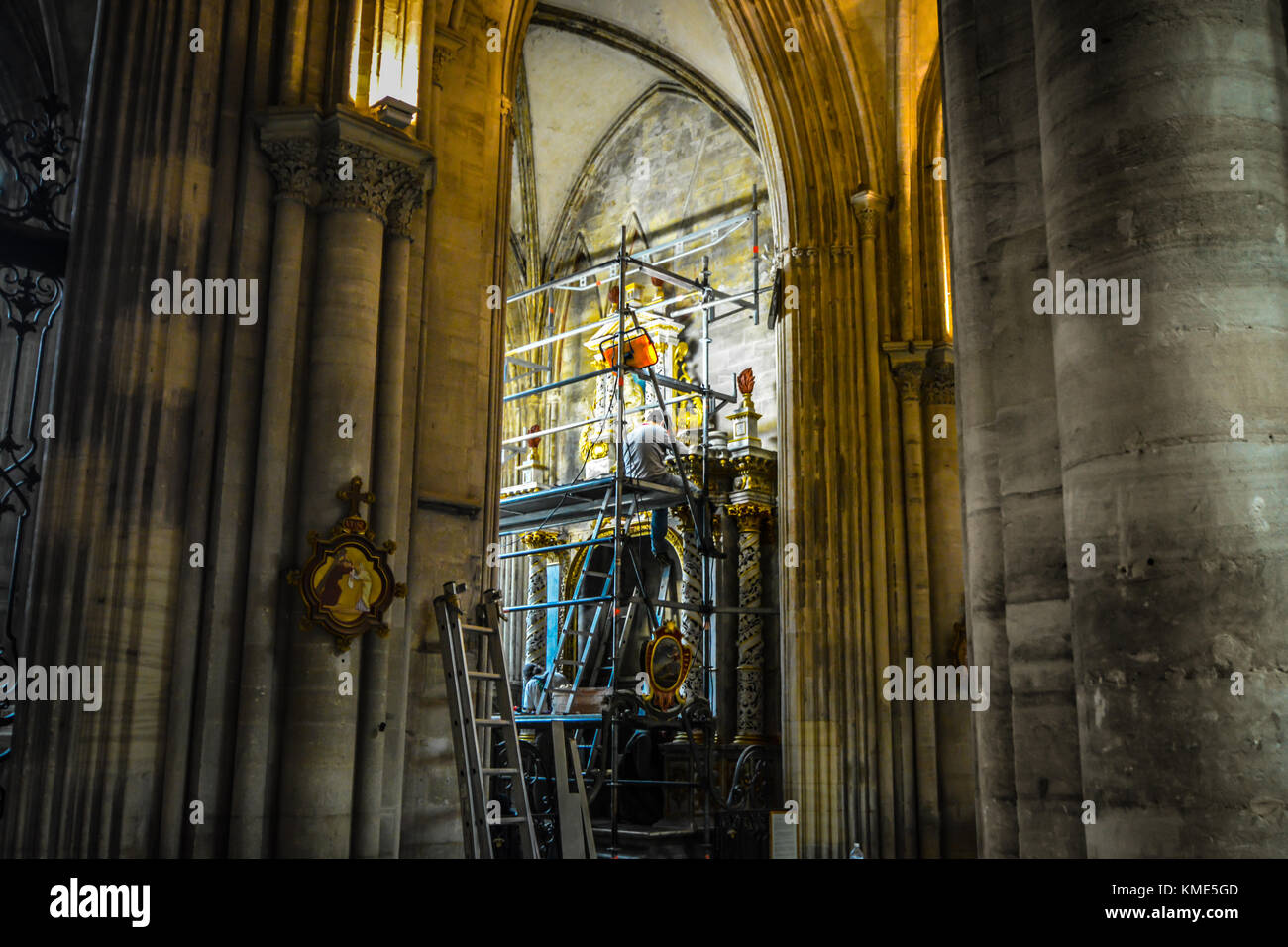 Historian restoring and renovation religious artwork from a scaffolding at the gothic Bayeux Cathedral in France - Stock Image