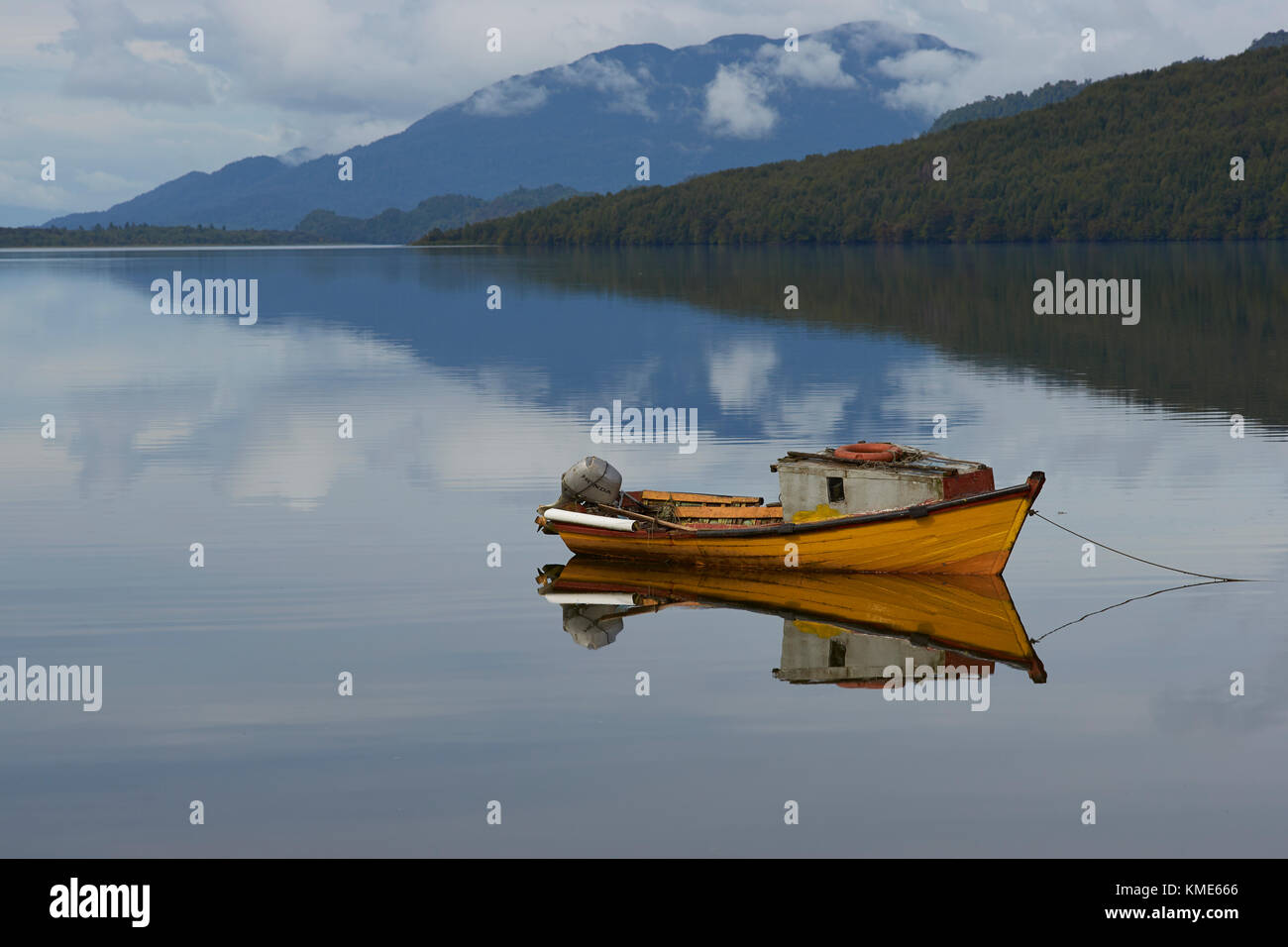 Small boat moored on the still waters of a sea loch at Puyuhuapi, a small town on the Carretera Austral in northern - Stock Image
