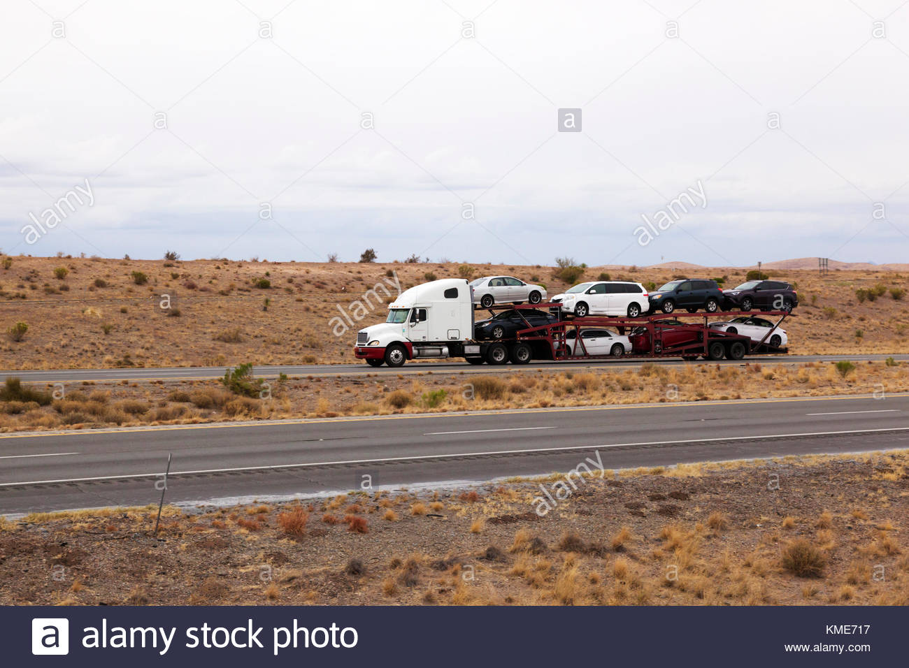 Semi-tractor pulling car hauler trailer on interstate in southeasterrn Arizona, USA, driver visible in cab Stock Photo