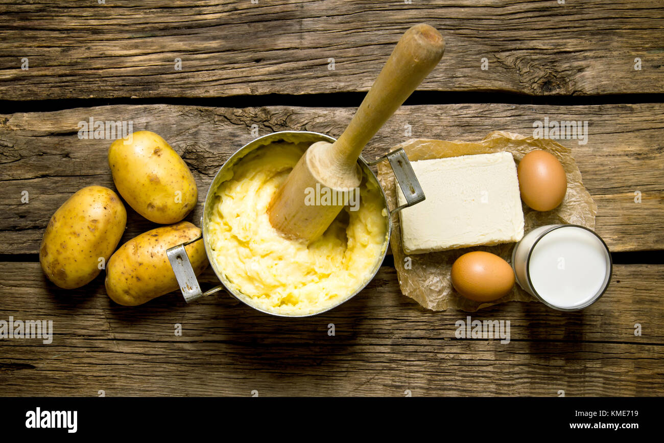 Potato food . Ingredients for mashed potatoes - eggs, milk, butter and potatoes on wooden background. Top view - Stock Image