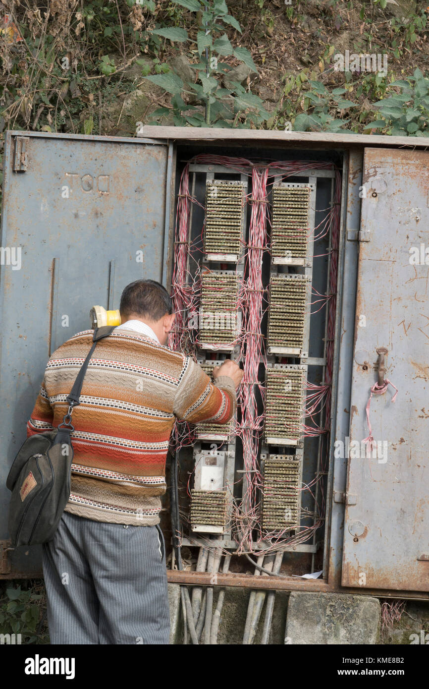 telecommunications technician works on phone lines in street telephone  wiring box at mcleod ganj india -