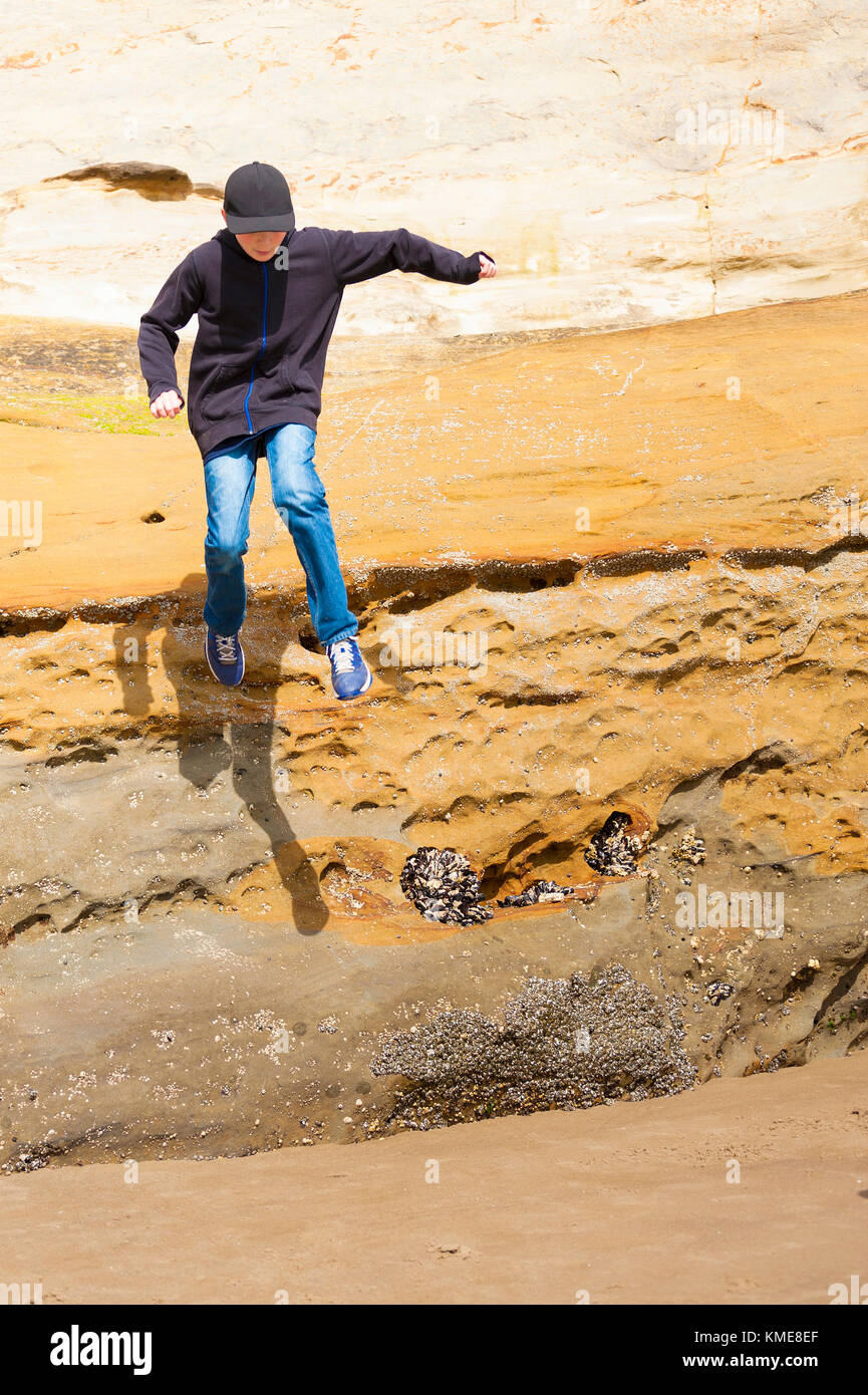 A young boy jumps from rocks on an Oregon Beach - Stock Image