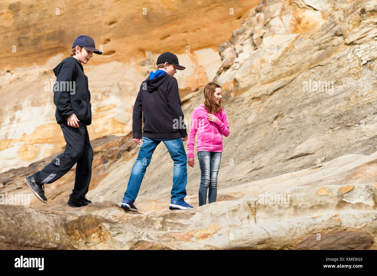 Two boys and a girl explore the sandstone geological feature at Cape Kiwanda in Pacific City on the Oregon Coast - Stock Image
