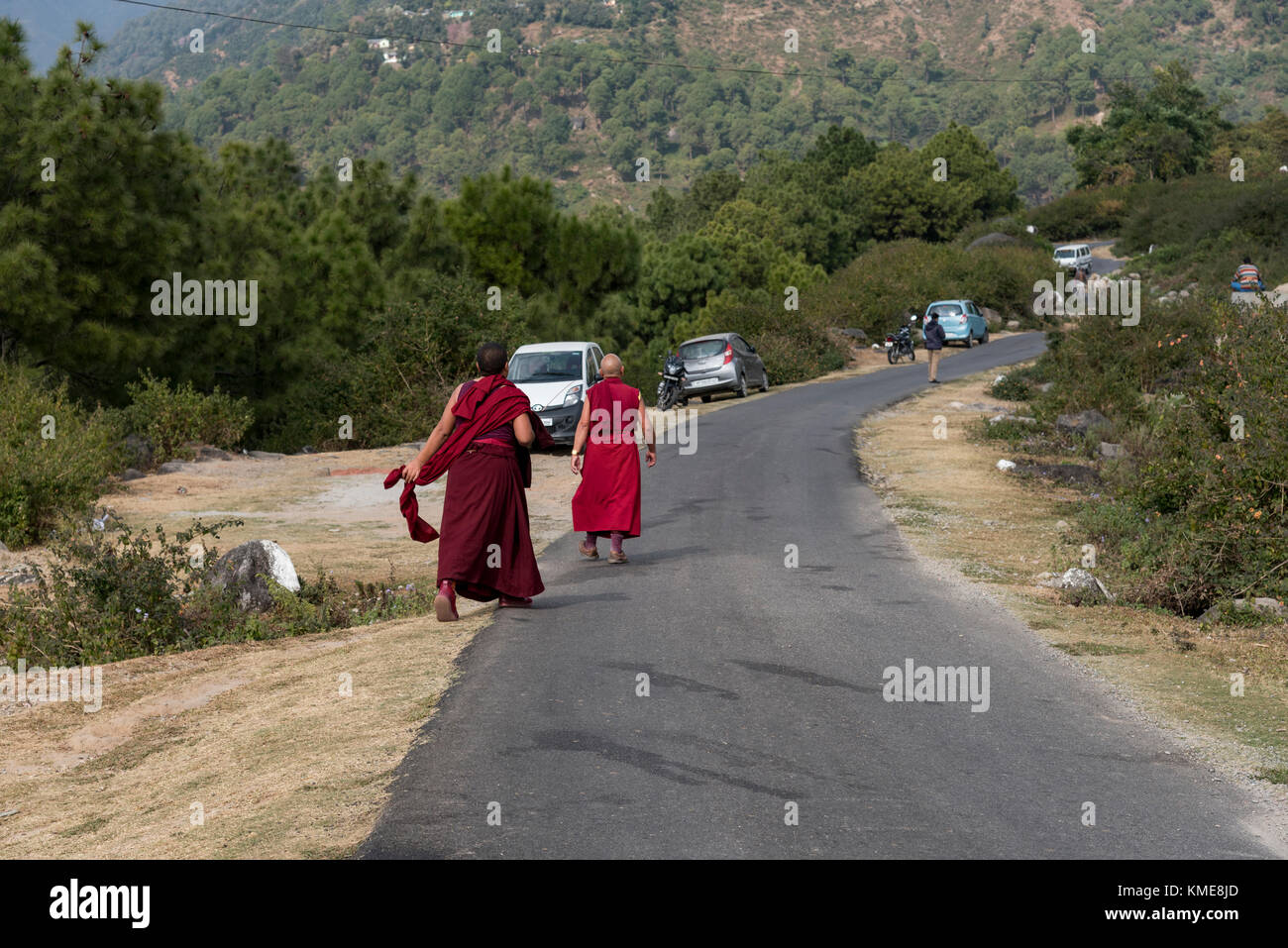 Two monks walking along the road in a rural area on the way to their monastery. - Stock Image