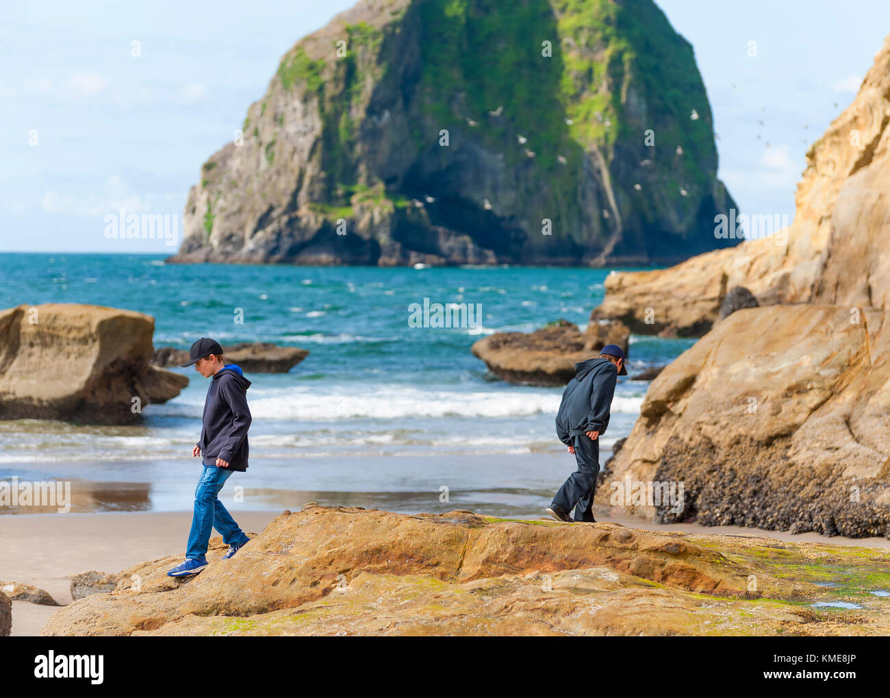 Two boys explore the tidepools at Cape Kiwanda in Pacific City, Oregon,  Landmark haystack rock surrounded by the - Stock Image