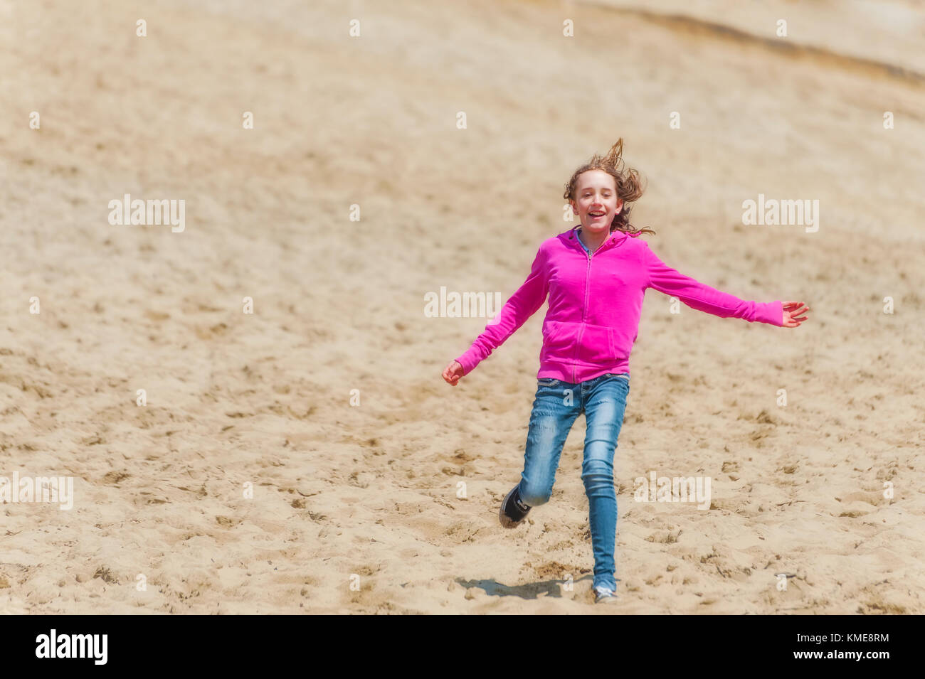A young girl wearing blue jeans and a pink sweatshirt is having fun running down a large sand hill at Pacific City - Stock Image