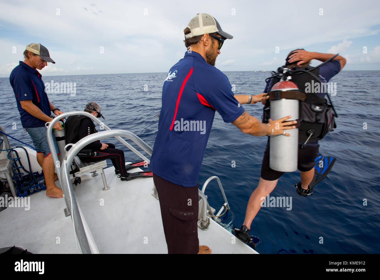 Boat crew assists scuba divers entering water Stock Photo